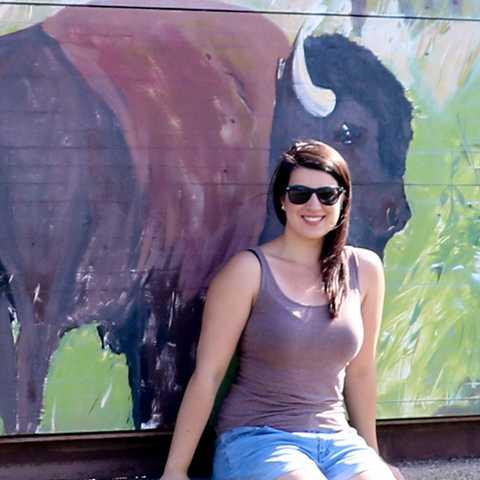 Mitarbeiterin Sarina am Schild des Elk Island Nationalparks