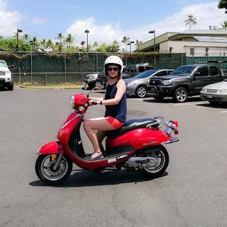 Mitarbeiterin Laura auf einem Moped in Honolulu, Hawaii
