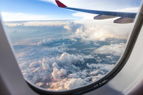 Wolken und Weite aus einem Flugzeugfenster beobachtet