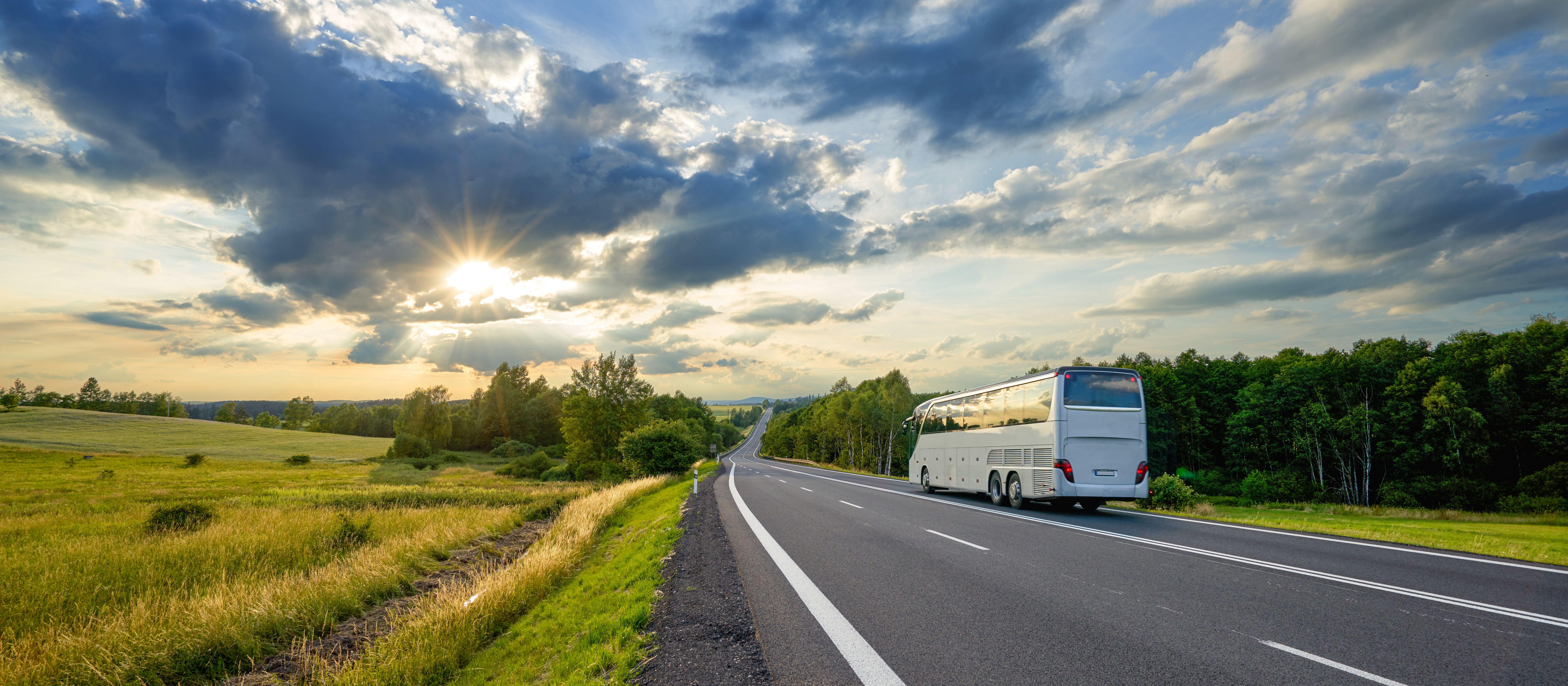 Ein Bus fährt auf einer Landstraße Richtung Sonnenuntergang