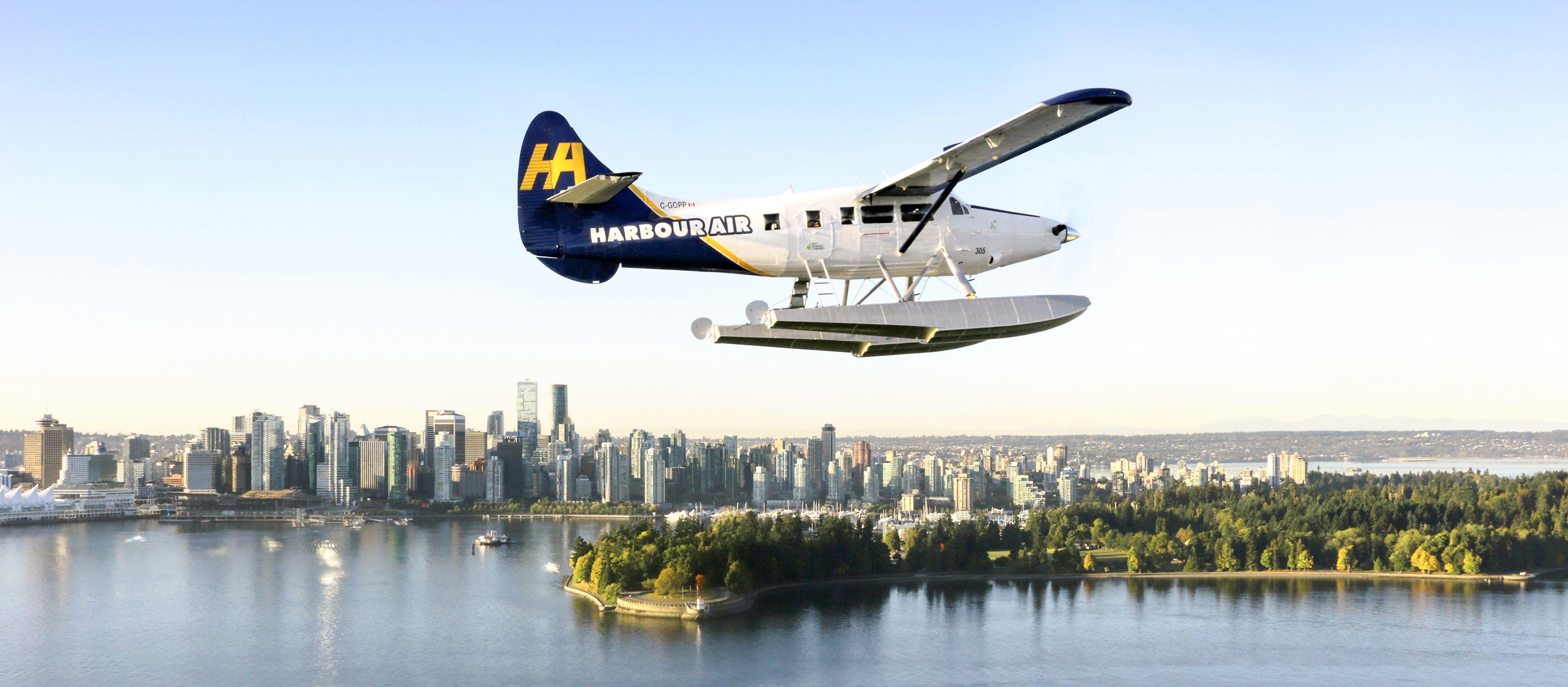 Ein Wasserflugzeug der Harbour Air vor der Skyline von Vancouver in Kanada