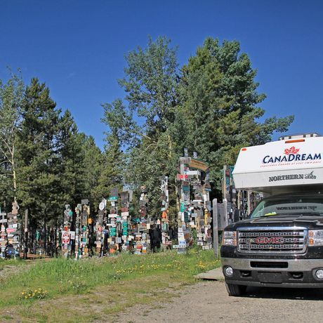 Ein CanaDream TCA Truck Camper in Watson Lake Signpost Forest auf dem Alaska Highway in Yukon