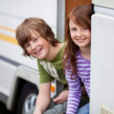 Kinder sitzen in der Tür eines Campers