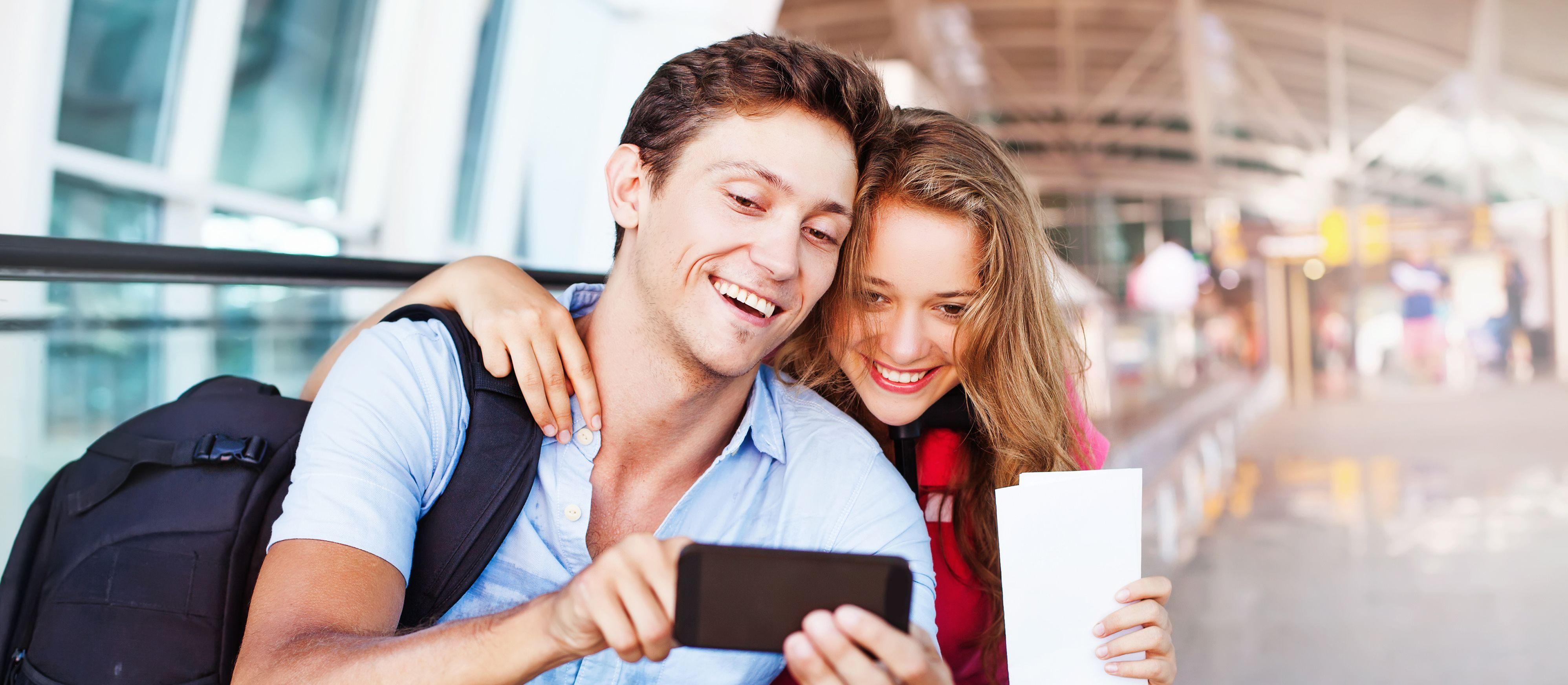 Ein Pärchen verwendet am Flughafen eine Reise-App auf ihrem Handy