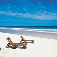 Zwei Liegen am Strand nahe dem Coral Sands Resort auf den Bahamas