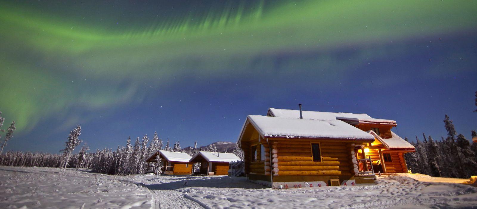 NWT Winter-Promo Yukon, Northern Lights Resort & Spa, Nordlichter über der Lodge