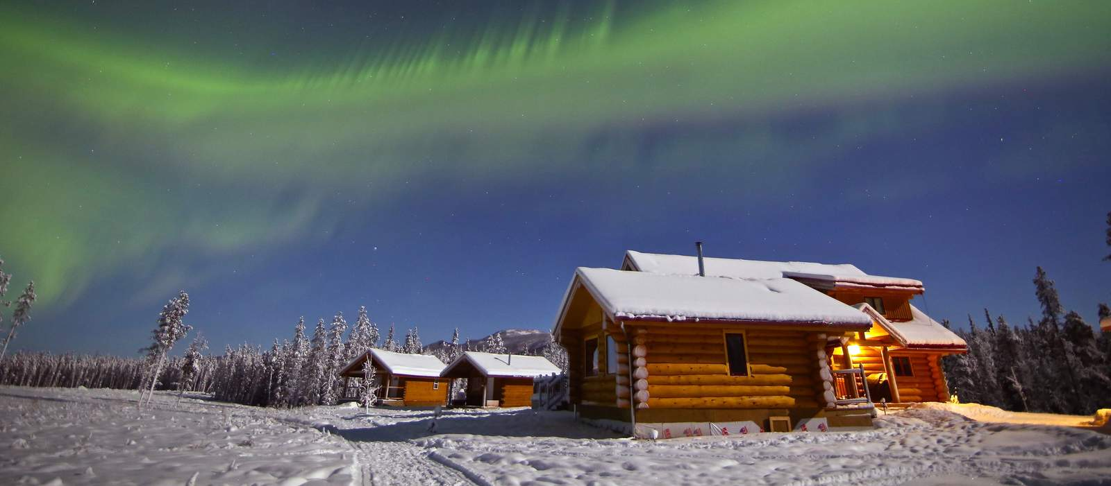 NWT Winter-Promo Yukon, Northern Lights Resort & Spa, Nordlichter über der Lodge
