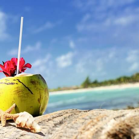 Kokosnuss mit Strohhalm am Strand