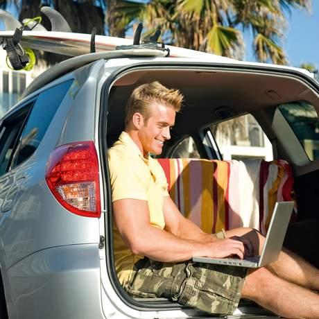 Junger Mann sitzt mit seinem Laptop im Kofferraum