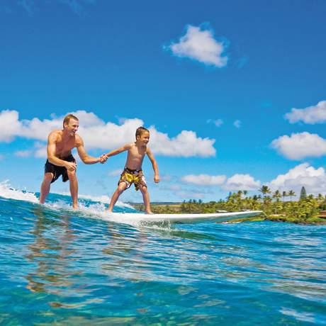 Vater und Sohn surfen auf einer Welle