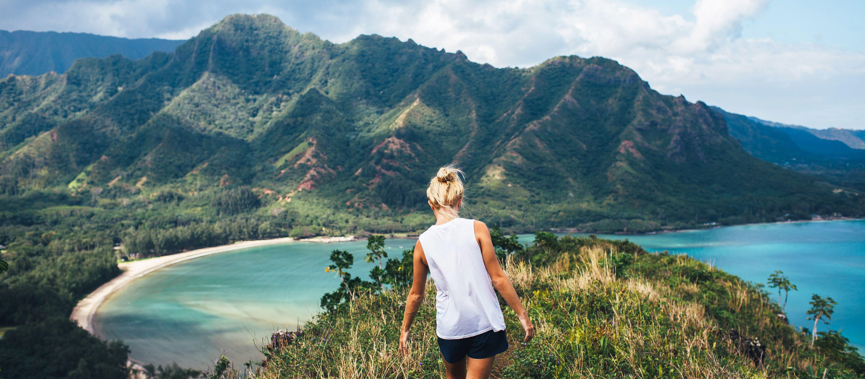 Eine junge Frau genießt während einer Wanderung die Weite Hawaiis