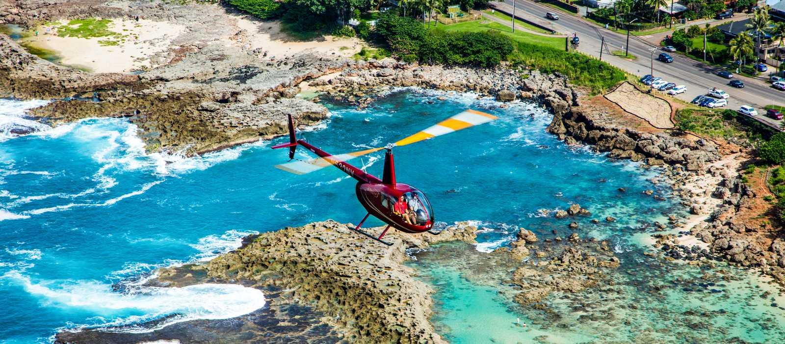 Ein Helikopter der Novictor Helicopter Company über der Insel O'ahu