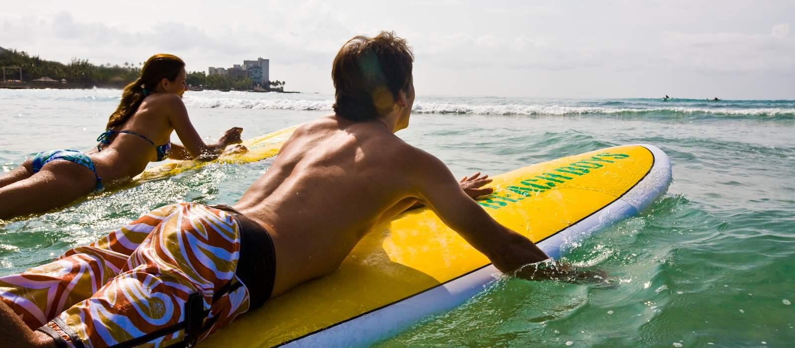 Couple going surfing off Waikiki Beach