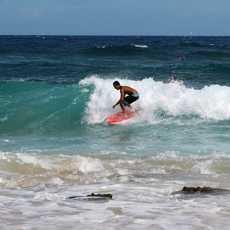 Ein Surfer an der Küste der hawaiischen Insel O'ahu