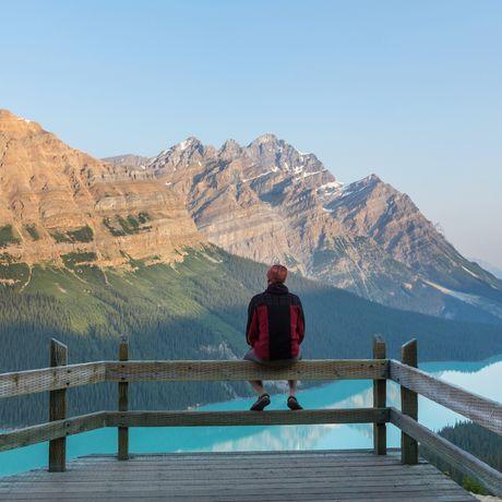 Mann sitzt am Peyto See, Alberta