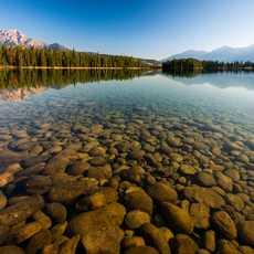 Kieselsteine im klaren Wasser des Lac Beauvert mit Pyramid Mountain im Jasper National Park, Alberta
