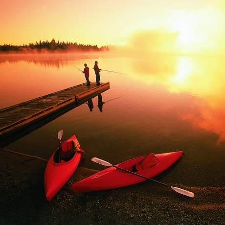 Angler auf einem Steg im Morgenrot über Manitoba, Kanada
