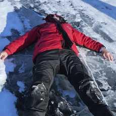 Mann liegt auf dem Eis bei Yelloknife