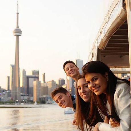 Jugendliche auf einer Bootstour mit Blick auf den Toronto CN Tower