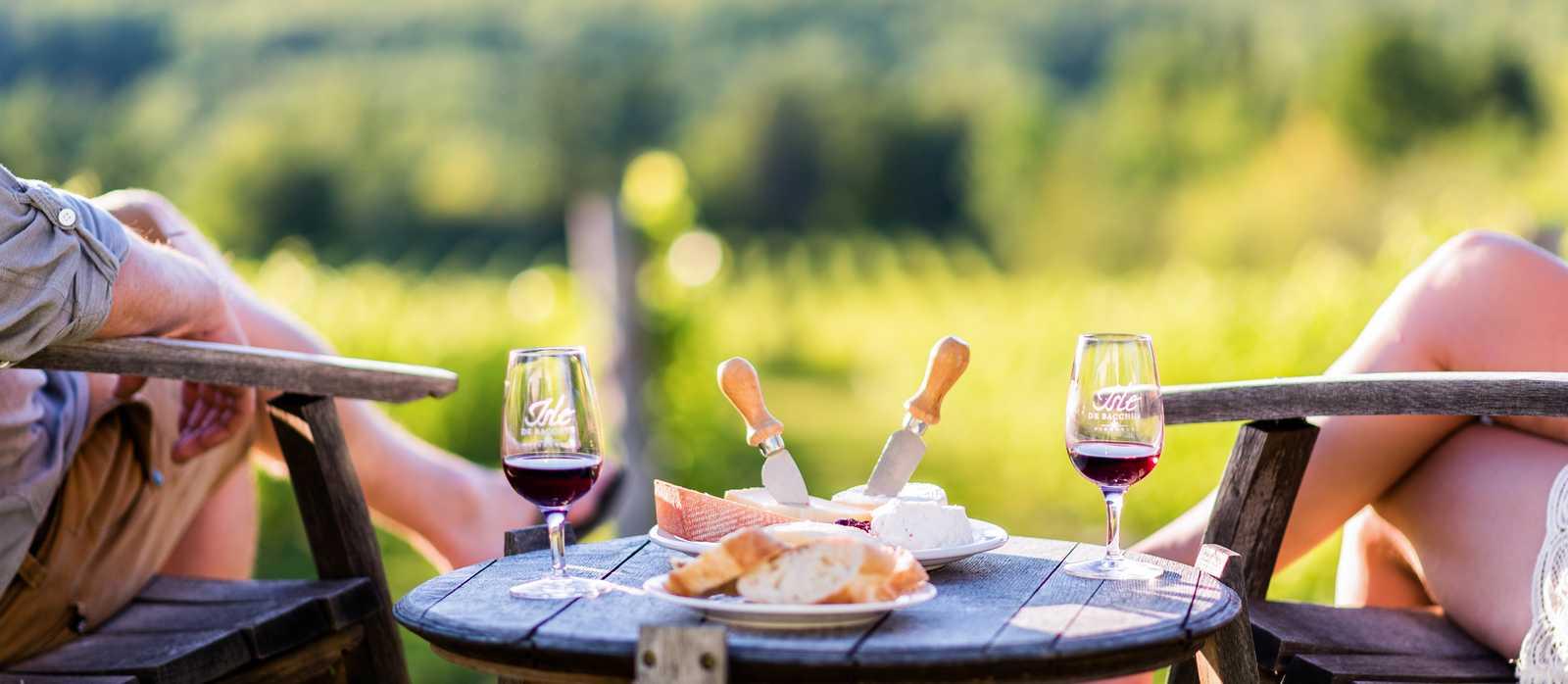 Ein Paar genießt Wein und Käse mit Blick auf den Sankt-Lorenz-Strom in Québec