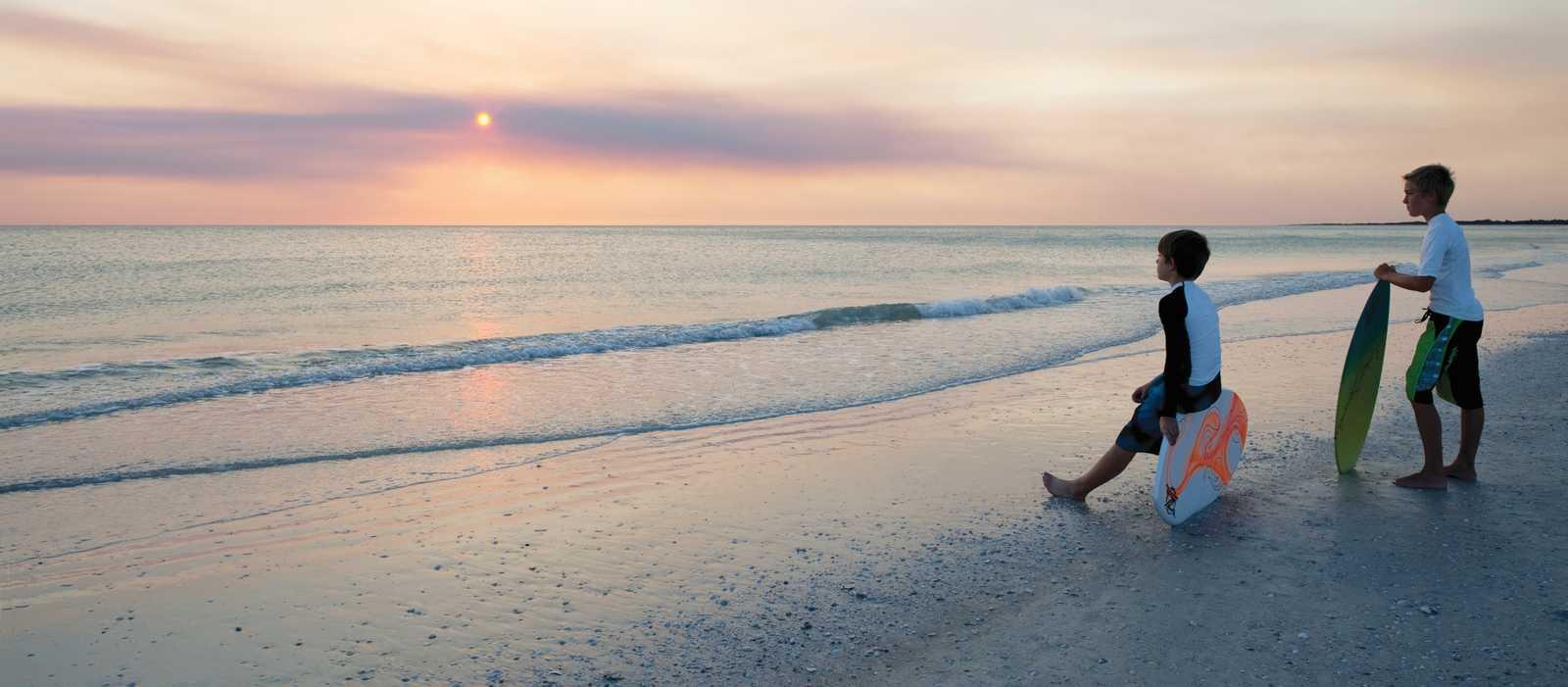 Skimboarders beim Sonnenuntergang am Strand von Naples