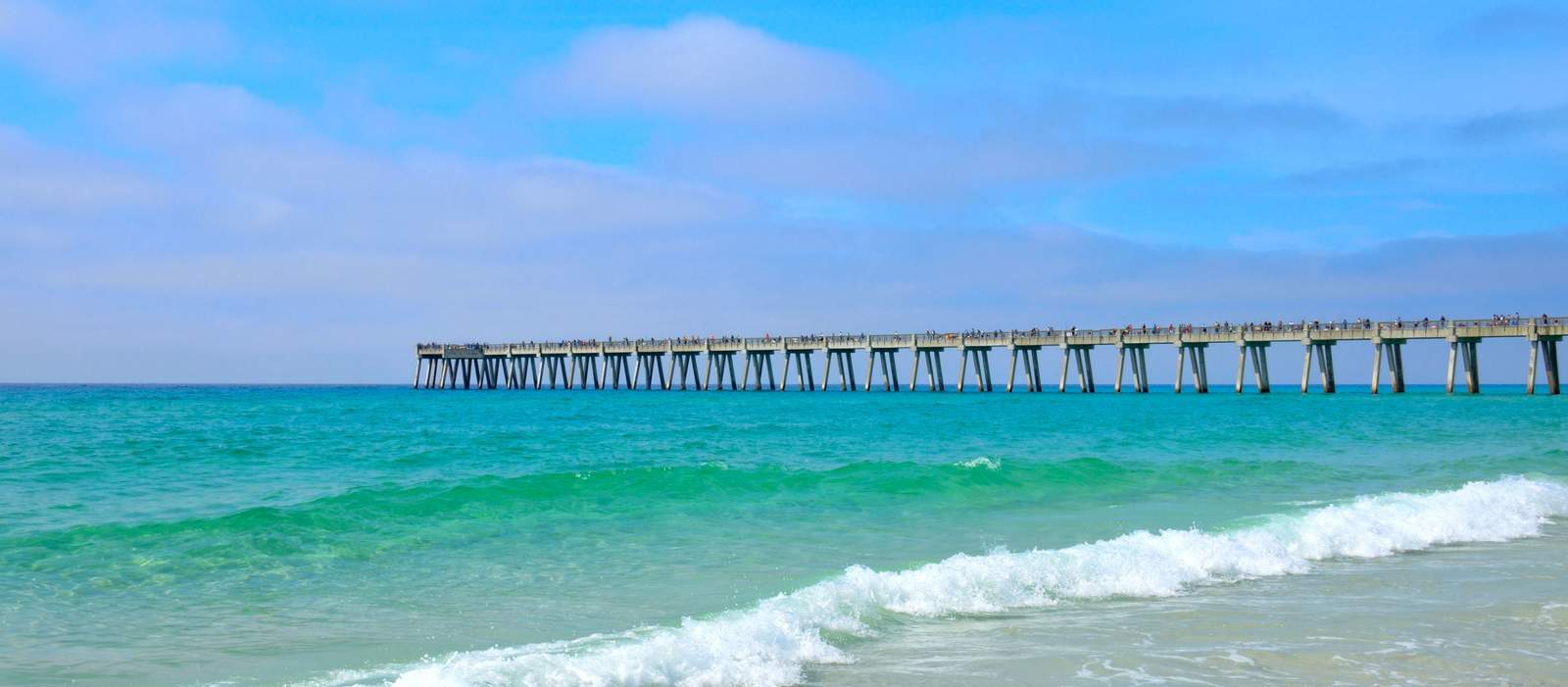 Pier extending out over the blue green ocean at Panama City
