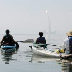 Mike Mahan (L), owner of Day Away Kayak Tours in Titusville, Florida, leads a group of 14 kayaks to Mosquito Lagoon in the Merritt Island Wildlife Refuge to watch the space shuttle Discovery lifts off the launch pad at Kennedy Space Center July 26, 2005. REUTERS/Mark Wallheiser
