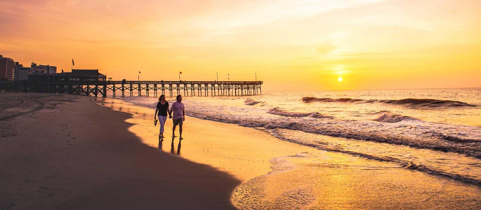 Bei Sonnenuntergang am Strand von Myrtle Beach entlang spazieren