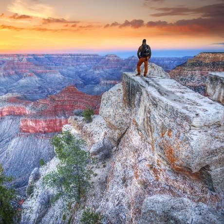 Ein Mann bei Sonnenaufgang im Grand Canyon