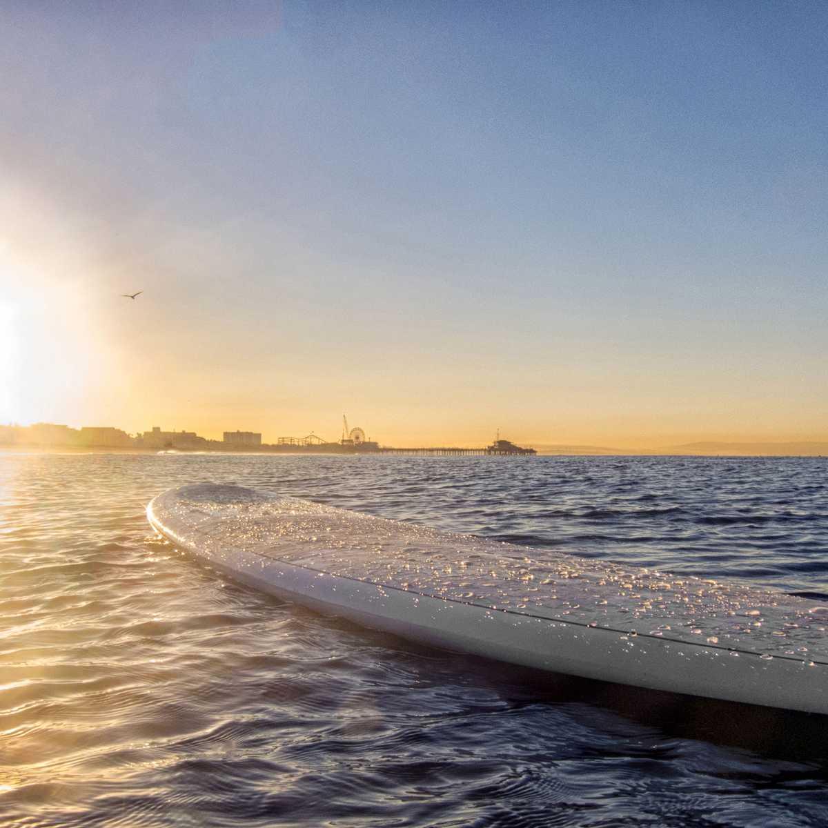 Surfbrett im Wasser mit der Santa Monica Pier und dem Pacific Park im Hintergrund, Kalifornien
