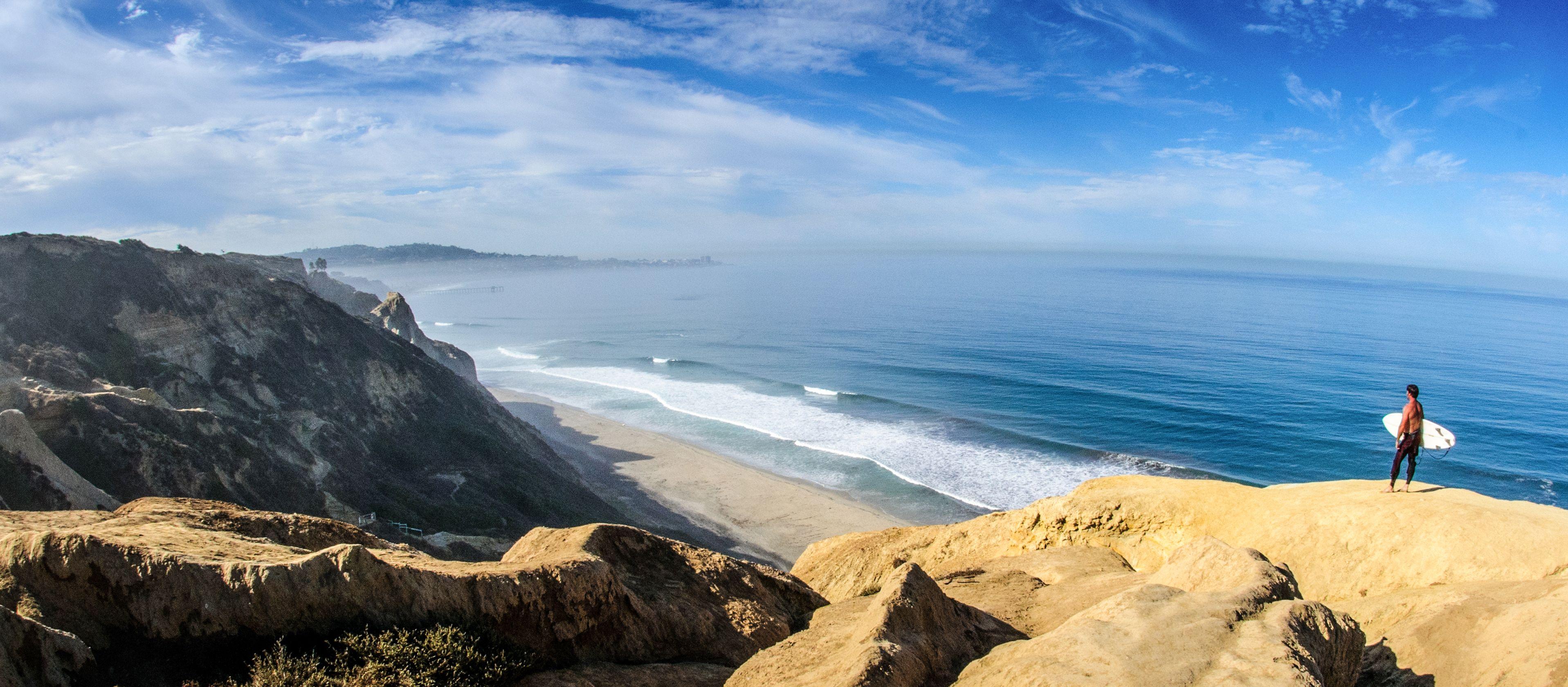 Ein Surfer beobachtet die Wellen am Strand von San Diego