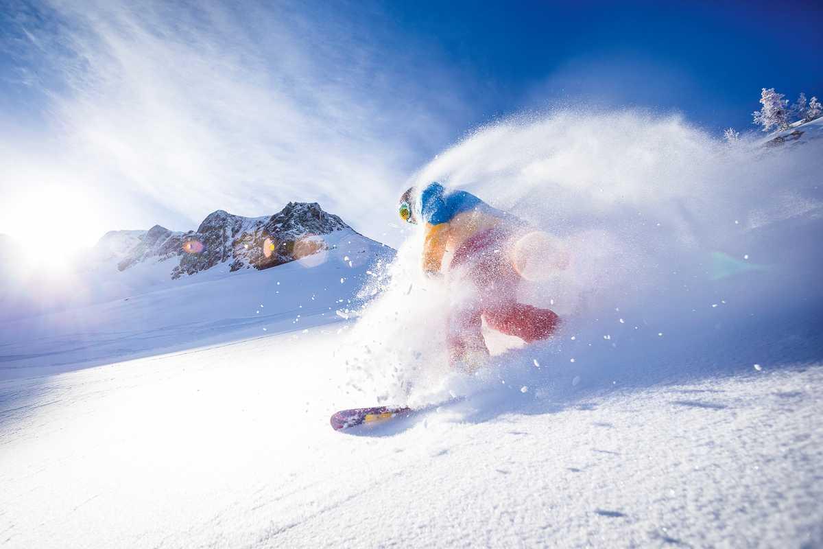 Snowboarder fährt durch den frischen Schnee