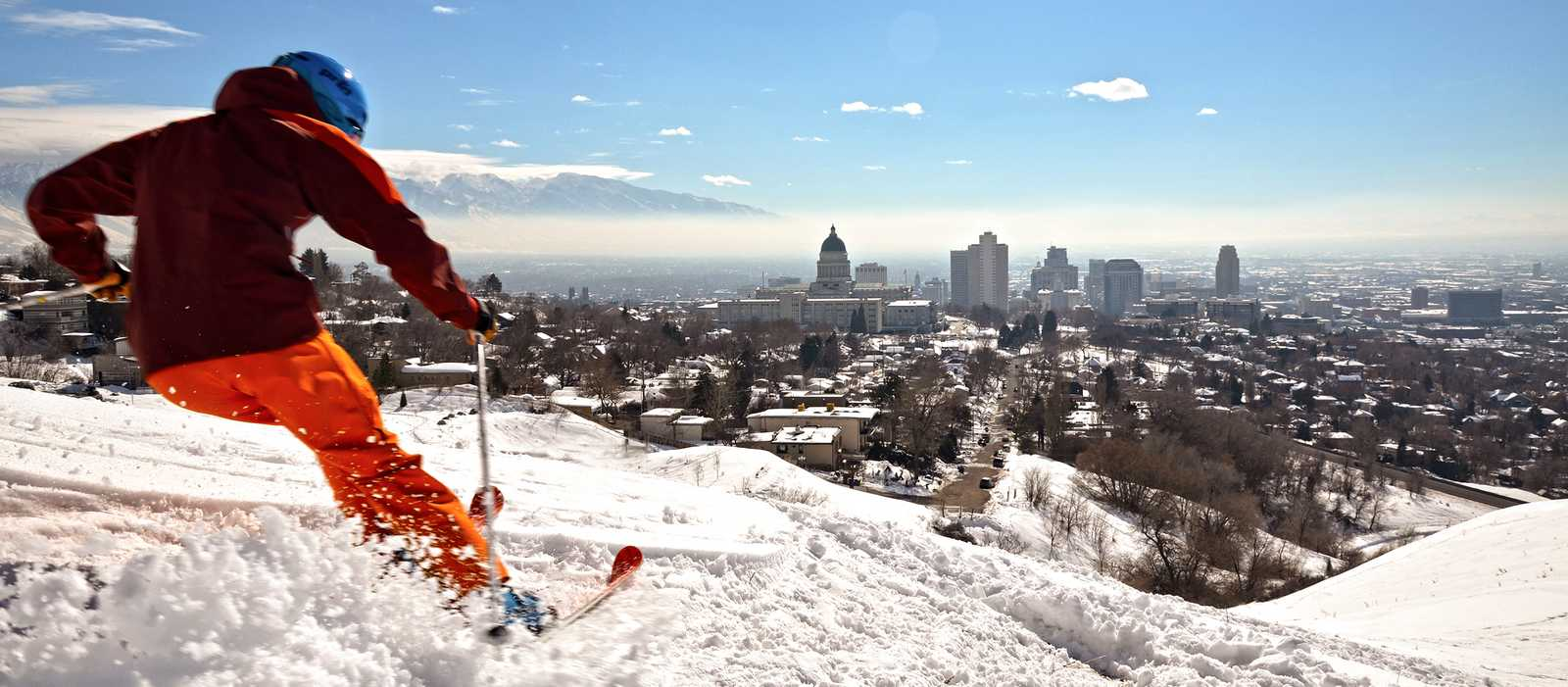 Ein Skifahrer vor der Skyline von Salt Lake City, USA
