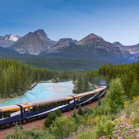 Zug der Rocky Mountaineer Bahngesellschaft vor Bergpanorama nahe Exshaw